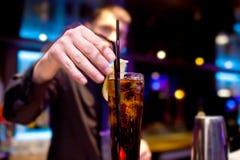 El camarero adorna la rebanada de vidrio del limón de la bebida efervescente Imagen de archivo libre de regalías