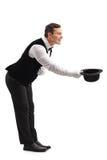 El camarero arquea abajo y sacando su sombrero Imágenes de archivo libres de regalías
