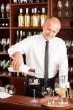El camarero de la barra de vino vierte el vidrio en restaurante Fotografía de archivo