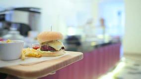 El camarero de la muchacha entrega la hamburguesa almacen de metraje de vídeo