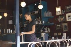 El camarero de la muchacha limpia platos de las tablas en el café imágenes de archivo libres de regalías