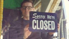 El camarero de sexo masculino atractivo en delantal está cambiando la placa de puerta del ` triste nosotros es ` cerrado al ` que almacen de metraje de vídeo