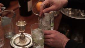 El camarero de sexo masculino revuelve el hielo con un cóctel en un vidrio metrajes