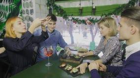 El camarero en delantal está sirviendo el aperitivo a la gente joven La mujer toma una foto de la comida en la tabla almacen de video
