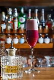 El camarero en la barra vierte un cóctel alcohólico en un vidrio con una corriente potente, no asustada derramarse en la tabla Foto de archivo