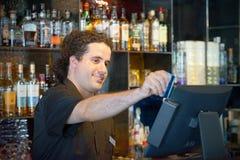 El camarero en la caja registradora Imágenes de archivo libres de regalías