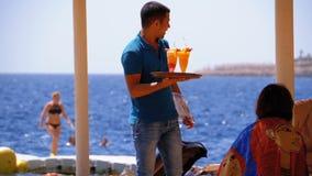 El camarero en la playa lleva los jugos y los cócteles frescos exóticos en una bandeja en Egipto C?mara lenta almacen de video