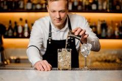 El camarero en el pub vierte el whisky en el hielo en vidrio Foto de archivo libre de regalías