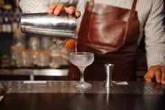 El camarero en un delantal marrón vierte de un cóctel de acero del alcohol de la coctelera Fotografía de archivo