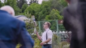 El camarero en una camisa blanca y gafas de sol es botellas que hacen juegos malabares muy frescas delante de la audiencia almacen de metraje de vídeo