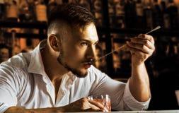 El camarero encantador prueba elegante una bebida mezclada de un spo de la barra foto de archivo