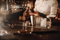 El camarero está añadiendo el ingrediente en coctelera en el contador de la barra Imágenes de archivo libres de regalías