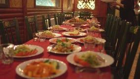 El camarero está fijando las tablas en el restaurante para celebrar la celebración almacen de metraje de vídeo