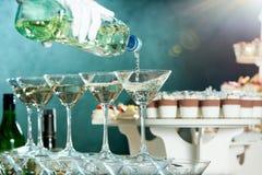 El camarero está vertiendo martini en vidrios en el fondo del abastecimiento Fotos de archivo libres de regalías