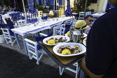El camarero está sirviendo el calamar asado a la parrilla en la placa en un restaurante Fotografía de archivo