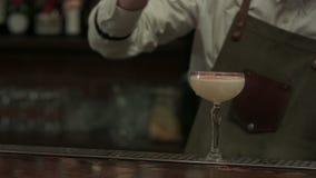 El camarero experto está vertiendo se preparó en cóctel de la coctelera a un vidrio y lo puso en servilleta en el club de noche almacen de metraje de vídeo