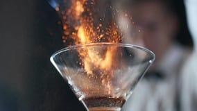 El camarero fija el fuego al cóctel, canela ardiente en la bebida del alcohol, 240 secuencias por segundo, camarero hace la bebid almacen de metraje de vídeo