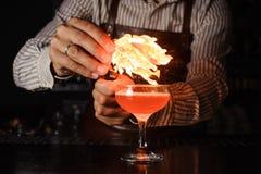 El camarero hace la llama sobre el cóctel Fotografía de archivo libre de regalías