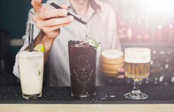 El camarero hace los cócteles en barra del club de noche Fotos de archivo