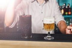 El camarero hace los cócteles en barra del club de noche Imágenes de archivo libres de regalías