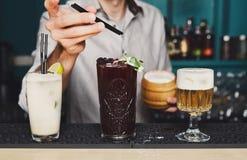 El camarero hace los cócteles en barra del club de noche Foto de archivo