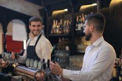 El camarero hermoso es sonriente y de relleno de un vidrio de la cerveza mientras que se coloca en el contador de la barra en pub fotografía de archivo