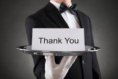 El camarero Holding Plate With el texto le agradece en el papel Foto de archivo