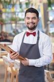 El camarero joven atractivo está trabajando en restaurante foto de archivo libre de regalías