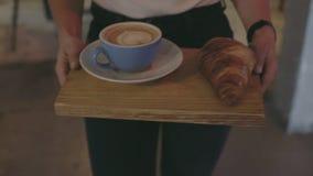El camarero lleva el café y el cruasán para presentar en el café metrajes