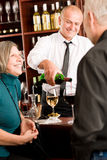El camarero mayor de los pares de la barra de vino vierte el vidrio Imágenes de archivo libres de regalías