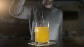 El camarero mezcla los ingredientes con la cuchara larga de la barra en la cámara lenta, bebidas frescas en la barra, cócteles  metrajes