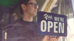El camarero ocupado de la cafetería en delantal está mirando afuera a través de la puerta de cristal y placa de puerta cambiante  metrajes