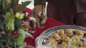 El camarero pone la ensalada de la tabla en envases individuales en un banquete en honor de la victoria almacen de metraje de vídeo