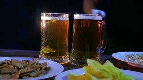 El camarero pone la tabla con bocados en las tazas llenas de un fondo dos negros de cerveza que hace espuma almacen de video