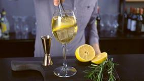 El camarero pone el limón y el romero en cóctel del alcohol con el vino espumoso, el hielo y el licor en la copa, opinión del pri metrajes