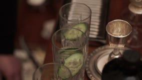 El camarero pone una rebanada de pepino en vidrio Preparación del cóctel en barra con el pepino almacen de video