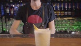 El camarero preparó el cóctel del huevo y lo da al cliente en el vidrio adornado con el limón El hombre joven hizo el cóctel sabr almacen de video