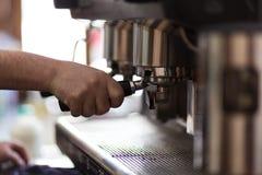 El camarero prepara el café con la máquina del coffe Imagen de archivo