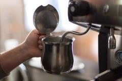 El camarero prepara la leche para el capuchino Fotografía de archivo libre de regalías