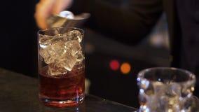 El camarero prepara un cóctel alcohólico delicioso La mano del camarero pone los cubos de hielo en un vidrio de whisky y almacen de video