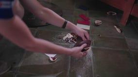 El camarero que coge junta las piezas de placas quebradas almacen de video