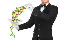El camarero que sostiene una placa de la ensalada de fruta envuelta en la medición de t Imágenes de archivo libres de regalías
