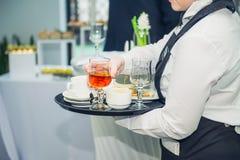 El camarero quita platos sucios de las tablas después de las huéspedes del evento Servicio del abastecimiento en la reunión de ne Foto de archivo libre de regalías