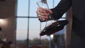 El camarero sacude el vino en una jarra en la cámara lenta, 240 secuencias por segundo, bebidas del alcohol, vino en restaurante almacen de video
