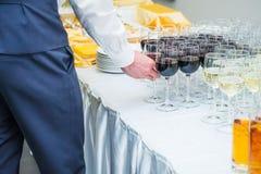 El camarero servering la tabla de comida fría del abastecimiento con las bebidas alcohólicas y sin alcohol en el evento del negoc Imágenes de archivo libres de regalías