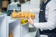 El camarero servering la tabla de comida fría del abastecimiento con la comida y los bocados para las huéspedes del evento Cena d Foto de archivo libre de regalías