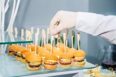 El camarero servering la tabla de comida fría del abastecimiento con la comida y los bocados para las huéspedes del evento Cena d Fotos de archivo