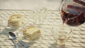 El camarero sirve el pastel de queso y vierte té almacen de video