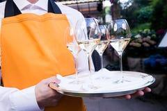 El camarero sostiene la bandeja con los vidrios Fotos de archivo