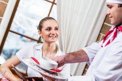 El camarero trae un plato para una mujer agradable Imagen de archivo